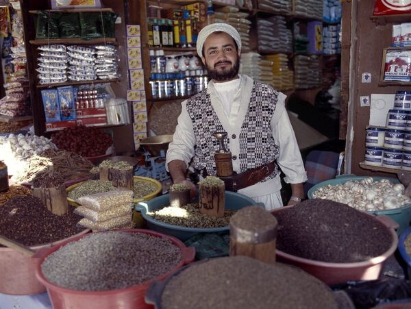 A Yemeni trader at his market stall in the old Suq. Surrounded by a massive 20 to 30-foot high wall, old Sana'a is one of the world's oldest inhabited cities. The suq or central market is located in a labyrinth of streets and alleyways in t