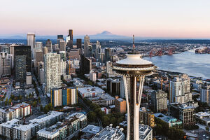 Aerial view of The Space Needle and downtown skyline at sunset with Mt Rainier in