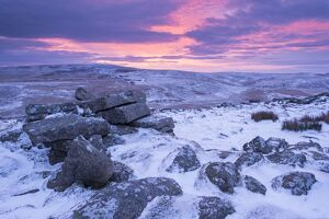 Beautiful sunrise over a frozen and snow covered Belstone Tor, Dartmoor National Park