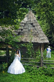 Bride stood in front of a traditional thatched roof