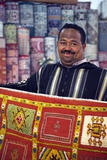 A carpet salesman displays his wares in the souq of Marrakesh