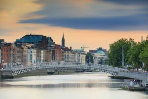 Europe, Dublin, Ireland, Half Penny bridge at sunset reflecting in the Liffey river