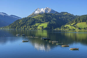 Fisher boats on Lake Wagital with Fluebrig mountain in the Glarner Alps at fall, Innerthal