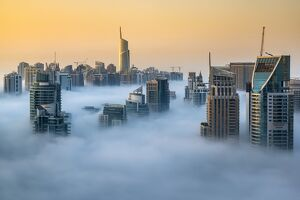 Foggy sunrise with Dubai Marinaa€™s skyscrapers towering over the low clouds, Dubai