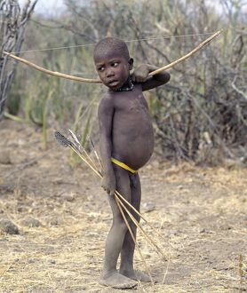 A Hadza boy carrying a bow and arrows.