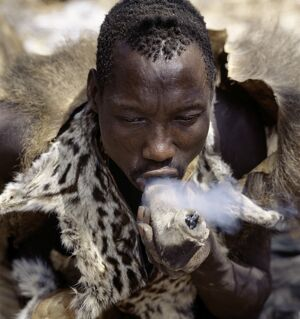 A Hadza hunter smokes cannabis from a crude stone pipe