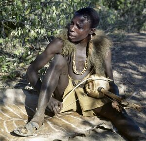 Hadza youth sings to the accompaniment of his two-stringed musical instrument.