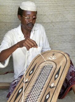 A Lamu man strings the back of a traditional Lamu-style