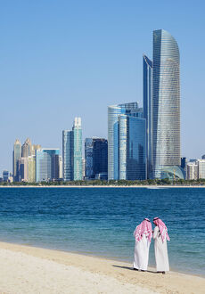 Two men wearing thawb on the beach and City Center Skyline, Abu Dhabi, United Arab