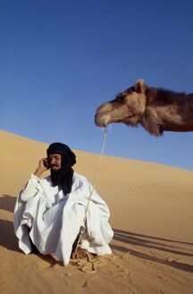 A nomad sits in the desert and talks on his mobile phone