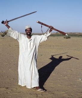 A Nubian man displays his sword at an oasis in the