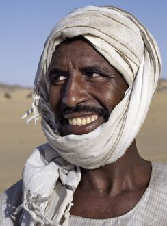 A Nubian man wearing a white turban smiles broadly at his friend