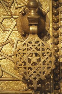 Ornate handle on gilt door at entrance to the Royal Palace